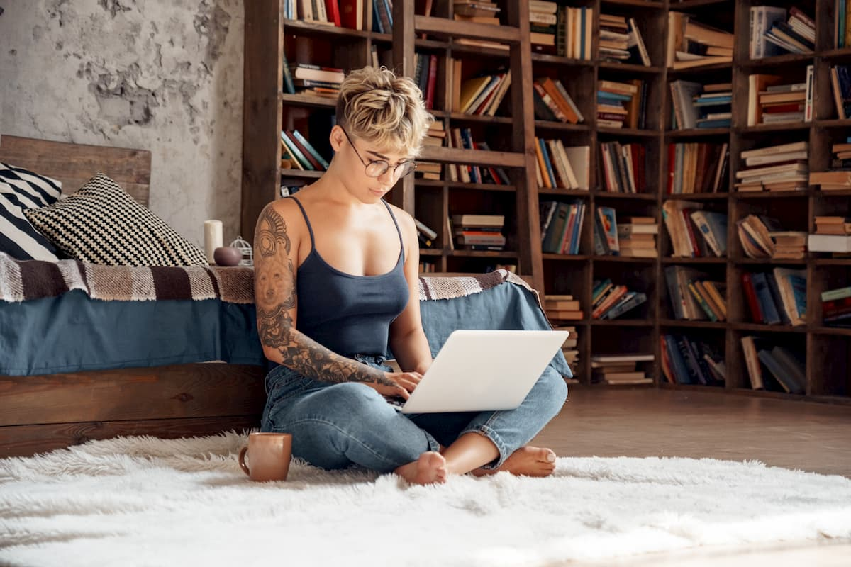 Young woman short hair in glasses sitting on floor working online on laptop - Post on what are the benefits of side hustle
